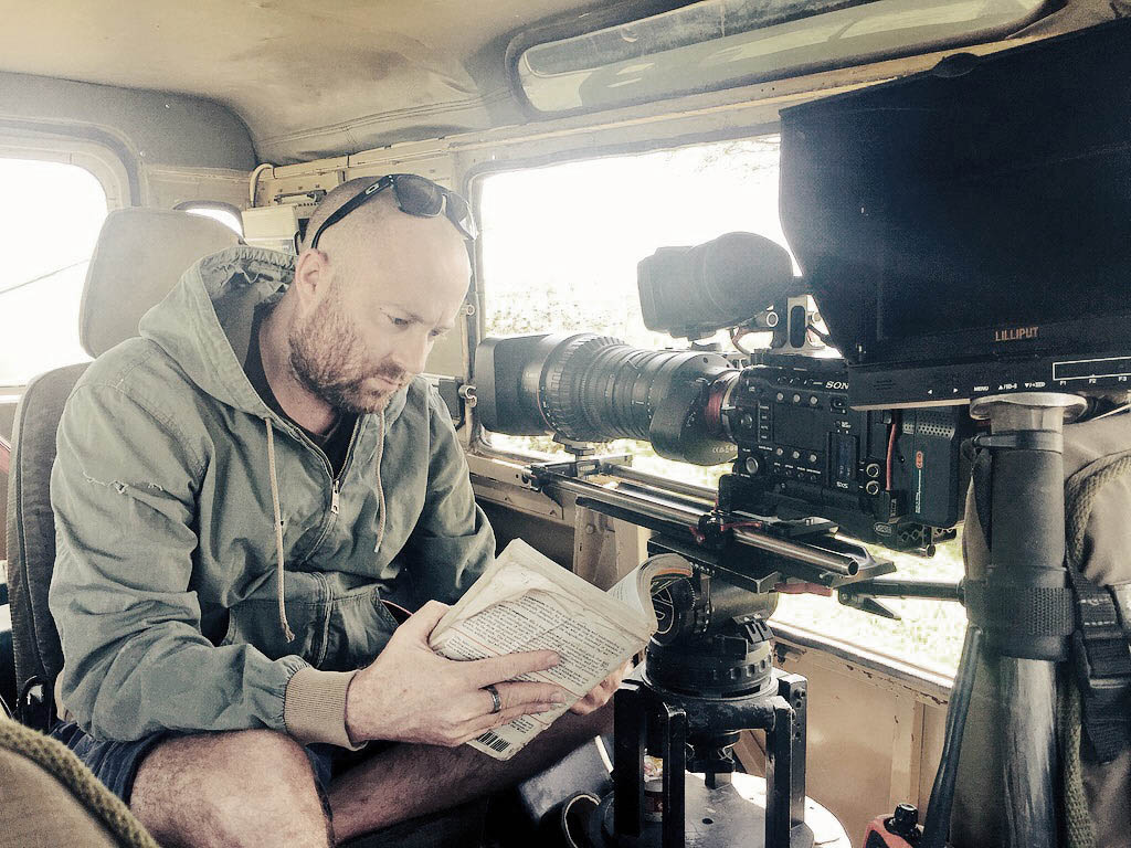 Nick Ball Wildlife Cameraman reading a book whilst waiting for wildlife, in front of his camera